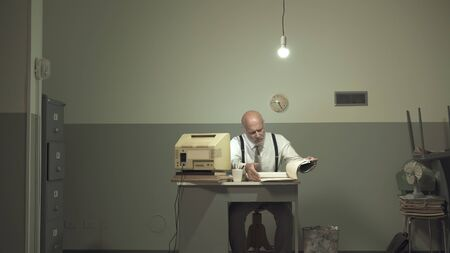 Sad vintage style businessman working in a small rundown office with an old computer and cheap furniture, he feels miserable and disappointed