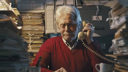 Senior businessman sitting at desk and answering phone calls, he is surrounded by piles of paperwork Imagens
