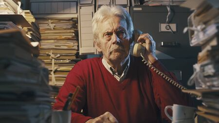 Senior businessman sitting at desk and answering phone calls, he is surrounded by piles of paperwork
