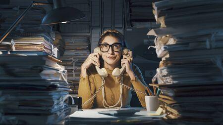 Gelangweilte stylische Sekretärin, die im Büro Telefonanrufe beantwortet, hält sie zwei Hörer gleichzeitig in der Hand Standard-Bild