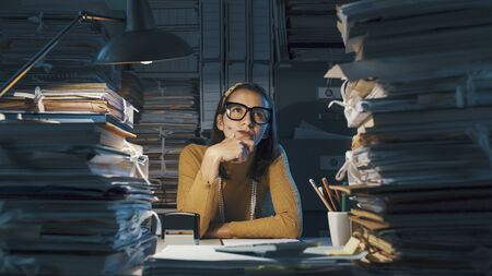 Pensive young businesswoman in the office, she is thinking with hand on chin surrounded by piles of paperwork