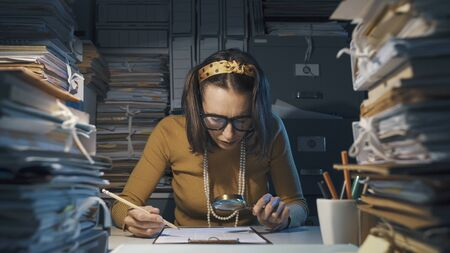 Efficient businesswoman sitting at office desk and checking a contract with a magnifier, she is surrounded by piles of paperwork