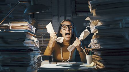 Angry stressed woman sitting at office desk screaming and crumpling paperwork, she is overloaded with work