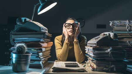 Stressed exhausted businesswoman working at desk late at night, she is thinking with head in hands