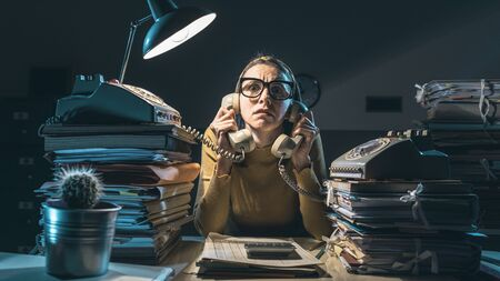 Frustrated secretary working overtime late at night, she is sitting at desk and answering many phone calls
