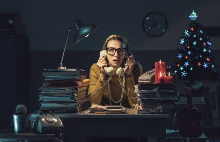 Unhappy stressed businesswoman working late at night in the office on Christmas Eve, she is holding two telephone receivers and answering phone calls Imagens
