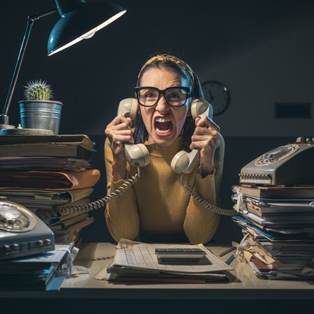 Angry stressed secretary working overtime and shouting at the customers on the phone