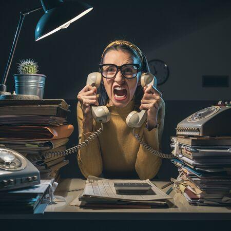 Wütend gestresste Sekretärin macht Überstunden und schreit die Kunden am Telefon an