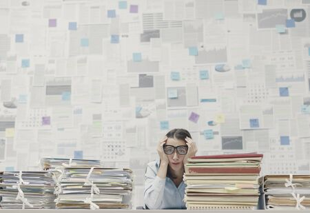 Stressed businesswoman with head in hands, she is sitting at office desk and she is overloaded with work, wall covered with financial reports in the background Imagens