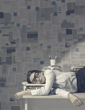 Exhausted business executive lying down on the desk and sleeping, wall covered with financial reports in the background, overtime work and deadlines concept