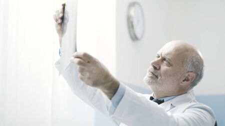 Professional senior doctor checking a patients radiography at the clinic, diagnosis and treatment concept Stock Photo