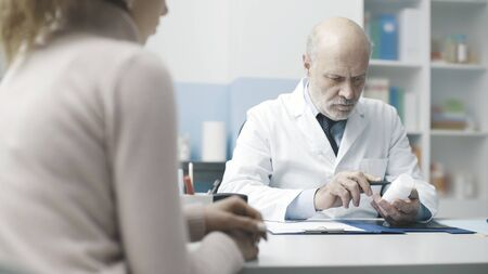 Professional senior doctor meeting a patient in the office and giving a prescription medicine