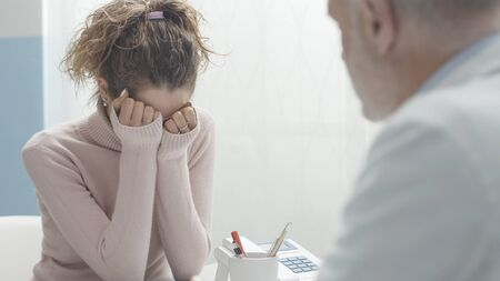 Sad woman meeting her doctor and receiving a bad diagnosis, she is desperate and crying