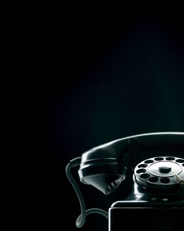 Vintage rotary dial phone on black background, low key silhouette Stock Photo