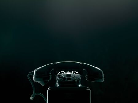 Vintage rotary dial phone on black background, low key silhouette Фото со стока