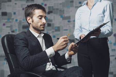 Corporate business executive signing a document, his assistant is holding a clipboard Stock Photo