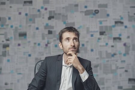 Young confident manager thinking with hand on chin and planning business strategies, wall with financial reports in the background