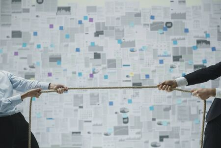 Business competition and challenges: businessman and businesswoman playing a tug of war and pulling rope Stock Photo