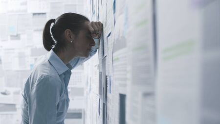 Depressed businesswoman leaning on a wall covered with financial reports, business failure concept
