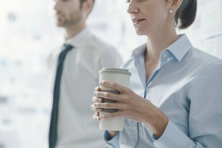 Business people having a meeting, the woman is holding a coffee and listening