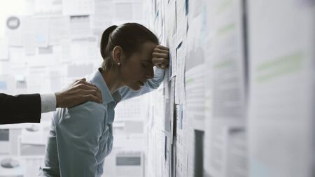 Depressed businesswoman leaning on a wall covered with financial reports and helping hand supporting her, business failure concept Stock Photo