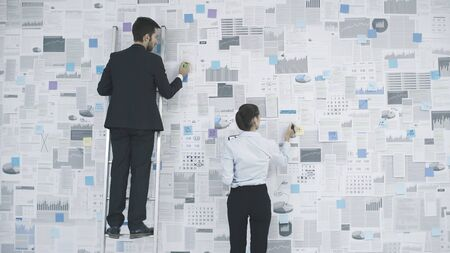 Corporate executives planning their business strategy: they are analyzing many financial reports and charts hanging on a wall Stock Photo