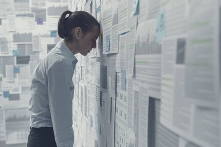 Exhausted depressed businesswoman leaning on a wall covered with financial charts and feeling hopeless, business failure concept Stock Photo