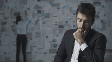Pensive businessman thinking about business strategies, his colleague is analyzing financial charts in the background