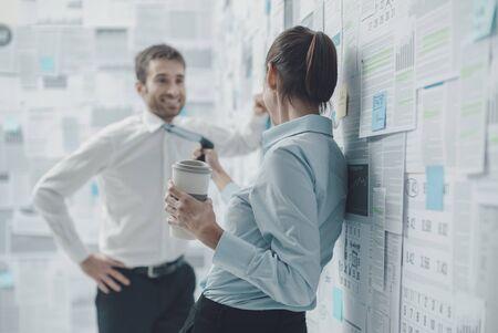 Compañeros de trabajo felices tomando un café juntos y coqueteando, la mujer está tirando de su corbata, conceptos de relaciones Foto de archivo