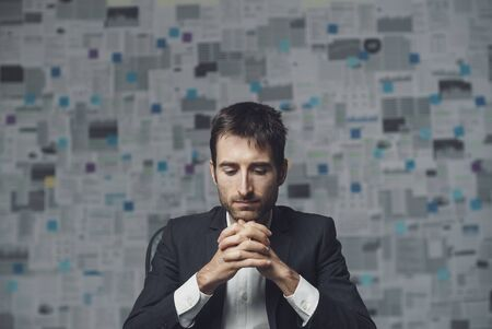 Corporate businessman thinking with hands clasped, he needs a solution for his business