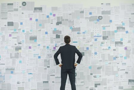 Corporate businessman standing with arms akimbo in front of a wall with lots of financial reports, business strategies and planning concept