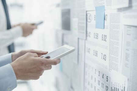 Corporate business team analyzing financial charts on a wall and planning business strategies, the woman is using management apps on a digital tablet Stock Photo
