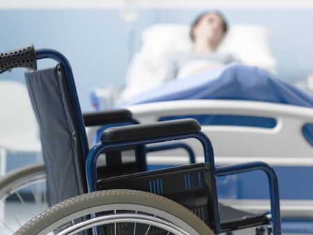 Hospitalized patient lying in bed and wheelchair in the foreground, medical treatment and injury concept