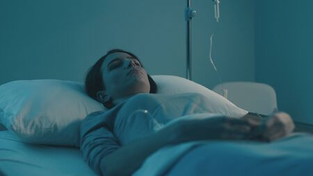 Young woman lying in a hospital bed at night and sleeping with IV drip Foto de archivo
