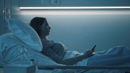 Sleepless worried patient lying in bed late at night at the hospital and chatting with her smartphone Stockfoto