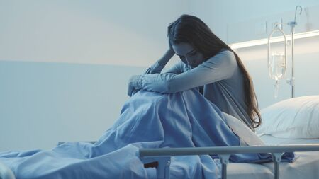 Sad female patient lying in the hospital bed at night, she is sleepless, lonely and worried