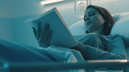 Young sleepless woman lying in the hospital bed at night and reading a book