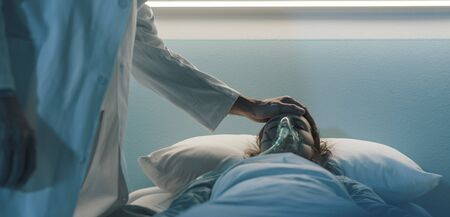 Doctor assisting a hospitalized patient at night and touching her forehead: she is lying in bed with an oxygen mask