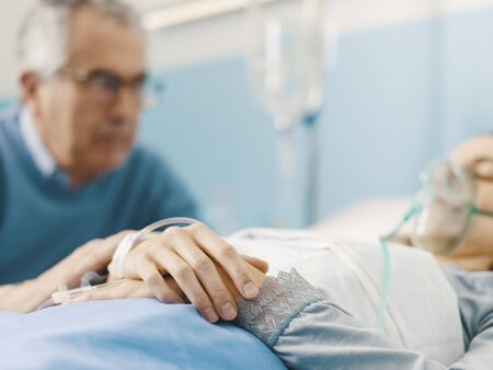 Caring concerned father assisting her sick daughter at the hospital and holding her hand, she is lying in bed and wearing an oxygen mask Stock Photo