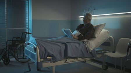 Lonely senior in a hospital bed suffering from insomnia at night, he is reading a book