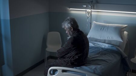 Depressed lonely senior sitting on a hospital bed at night, he is sad and looking down