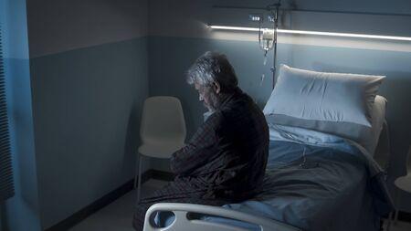 Depressiver einsamer Senior sitzt nachts auf einem Krankenhausbett, er ist traurig und schaut nach unten Standard-Bild