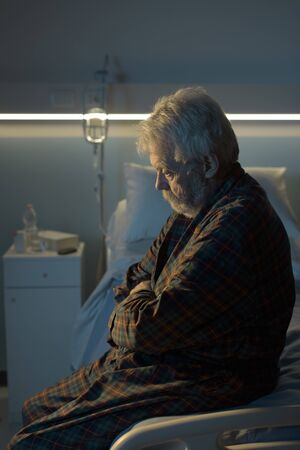 Depressed senior man sitting on the hospital bed alone at night, he feels lonely and abandoned Banque d'images