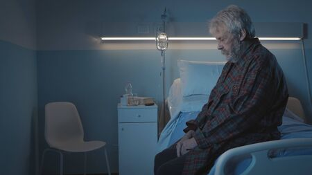Depressed senior man sitting on the hospital bed alone at night, he feels lonely and abandoned Stock Photo