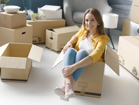 Smiling young woman moving in her new home, she is sitting in a cardboard box and smiling