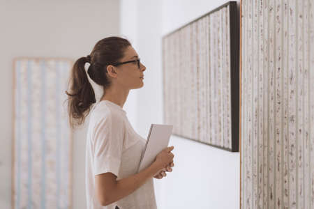 Woman with glasses visiting the art gallery and looking at the paintings, abstract art and art exhibition concept