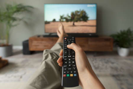 Woman watching TV on the couch at home and holding the remote control, point of view shot
