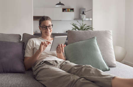 Woman relaxing on the sofa and connecting with her tablet in the living room