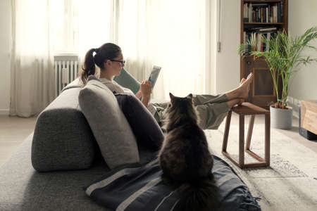 Woman relaxing on the sofa and connecting with her tablet at home