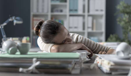 Exhausted businesswoman sleeping on her desk, she is tired and leaning on a pile of paperwork